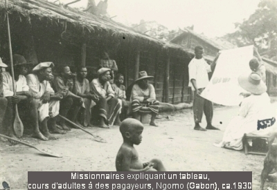 Missionnaires expliquant un tableau Missionnaires expliquant un tableau, cours d'adultes à des pagayeurs, Ngomo (Gabon), ca. 1930